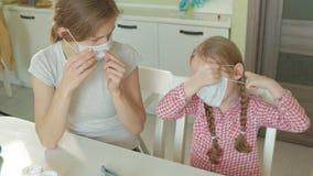 Νέα γυναίκα και κορίτσι που τίθενται στις ιατρικές μάσκες, τη μητέρα και την κόρη απόθεμα βίντεο