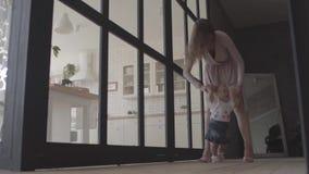 Νέα γυναίκα και το κοριτσάκι της που στέκονται στο πάτωμα στο σπίτι Το παιδί που κάνει το πρώτο βήμα, μητέρα την υποστηρίζει r απόθεμα βίντεο