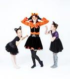 Νέα γυναίκα και δύο κορίτσια στην τοποθέτηση κοστουμιών καρναβαλιού γατών Στοκ Εικόνα