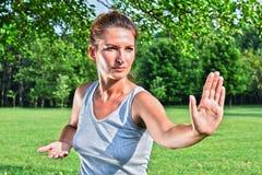 Νέα γυναίκα κατά τη διάρκεια tai chi της άσκησης στο πάρκο Στοκ Εικόνα