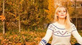 Νέα γυναίκα κατά τη διάρκεια της χαλάρωσης και της περισυλλογής στο πάρκο στοκ εικόνες