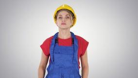 Νέα γυναίκα κατασκευής hardhat που περπατά στο υπόβαθρο κλίσης φιλμ μικρού μήκους