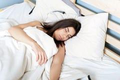 Νέα γυναίκα κοιμισμένη στο κρεβάτι της Στοκ Εικόνες