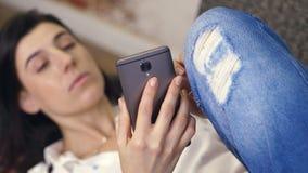 Νέα γυναίκα, κορίτσι, brunette, στο άσπρα πουκάμισο και τα τζιν, που βρίσκονται σε έναν καναπέ, μικρός καναπές, με το smartphone  φιλμ μικρού μήκους