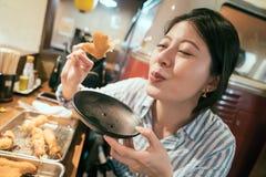 Νέα γυναίκα μετά από την εργασία που έχει το γεύμα στο izakaya στοκ φωτογραφία