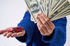 Νέα γυναίκα με ένα αυτοκίνητο και χρήματα παιχνιδιών υπό εξέταση στοκ φωτογραφία με δικαίωμα ελεύθερης χρήσης