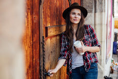 Νέα γυναίκα με ένα καπέλο δίπλα σε μια παλαιά ξύλινη πόρτα στοκ εικόνες