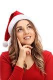 Νέα γυναίκα με ένα καπέλο Χριστουγέννων που κάνει μια επιθυμία Στοκ φωτογραφία με δικαίωμα ελεύθερης χρήσης