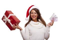 Νέα γυναίκα με ένα δώρο και χρήματα Χριστουγέννων Στοκ Φωτογραφίες