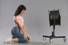 Νέα γυναίκα με αυξημένος από τη μηχανή αέρα Στούντιο που καλύπτονται πέρα από την γκρίζα ανασκόπηση στοκ εικόνα