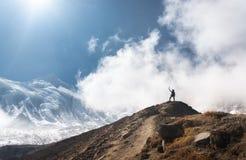 Νέα γυναίκα με αυξημένος επάνω στα όπλα στην αιχμή βουνών στοκ εικόνες