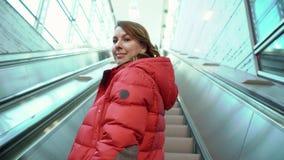 Νέα γυναίκα με μια βαλίτσα που περπατά στην κυλιόμενη σκάλα απόθεμα βίντεο