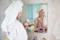 Νέα γυναίκα με μια πετσέτα στο λουτρό στοκ εικόνες