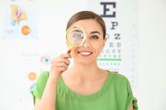 Νέα γυναίκα με πιό magnifier στοκ εικόνα με δικαίωμα ελεύθερης χρήσης
