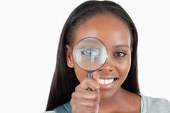Νέα γυναίκα με πιό magnifier Στοκ φωτογραφία με δικαίωμα ελεύθερης χρήσης