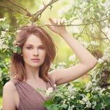 Νέα γυναίκα με τα άσπρα λουλούδια της Apple Στοκ Εικόνες