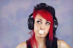 Νέα γυναίκα με τα ακουστικά με τη γόμμα φυσαλίδων Στοκ φωτογραφίες με δικαίωμα ελεύθερης χρήσης