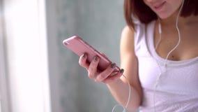 Νέα γυναίκα με τα ακουστικά που ακούει τη μουσική μετά από το σκληρό workout στη γυμναστική Το φίλαθλο κορίτσι με το ponytail είν απόθεμα βίντεο