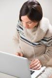 Νέα γυναίκα με τα ακουστικά που χρησιμοποιούν το lap-top Στοκ Φωτογραφίες