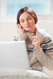 Νέα γυναίκα με τα ακουστικά που χρησιμοποιούν το lap-top Στοκ φωτογραφία με δικαίωμα ελεύθερης χρήσης