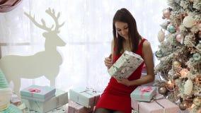 Νέα γυναίκα με τα δώρα Χριστουγέννων στο χριστουγεννιάτικο δέντρο στο εσωτερικό απόθεμα βίντεο