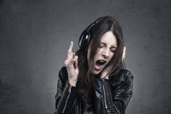 Νέα γυναίκα με τα επικεφαλής τηλέφωνα που ακούει τη μουσική και το τραγούδι Στοκ Εικόνες