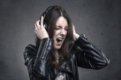 Νέα γυναίκα με τα επικεφαλής τηλέφωνα που ακούει τη μουσική και το τραγούδι Στοκ Εικόνα