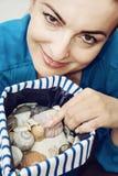 Νέα γυναίκα με τα διάφορα κοχύλια στην τσάντα ναυτικών Στοκ εικόνα με δικαίωμα ελεύθερης χρήσης
