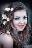 Νέα γυναίκα με τα λουλούδια στο τρίχωμα Στοκ εικόνα με δικαίωμα ελεύθερης χρήσης