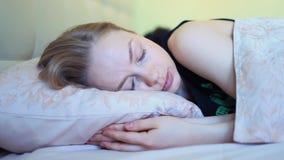 Νέα γυναίκα με τα μπλε μάτια που χαμογελά στο κρεβάτι μετά από να ξυπνήσει στα ξημερώματα φιλμ μικρού μήκους