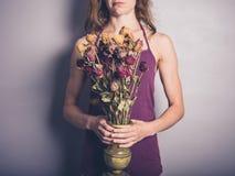 Νέα γυναίκα με τα νεκρά λουλούδια Στοκ Εικόνες