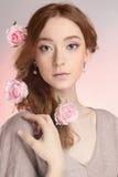 Νέα γυναίκα με τα λουλούδια στο τρίχωμα Στοκ Εικόνες