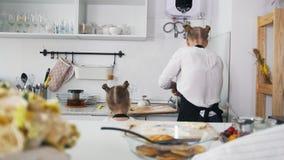 Νέα γυναίκα με τα πιάτα πλύσης κορών της μετά από να μαγειρεψει απόθεμα βίντεο