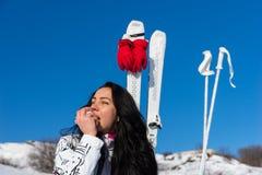 Νέα γυναίκα με τα σκι που τρώει τη Apple στη βουνοπλαγιά Στοκ φωτογραφία με δικαίωμα ελεύθερης χρήσης