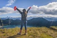 Νέα γυναίκα με τα χέρια επάνω στη λίμνη Quilotoa στοκ φωτογραφία