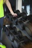 Νέα γυναίκα με τα barbells στο υπόβαθρο γυμναστικής Στοκ Εικόνες
