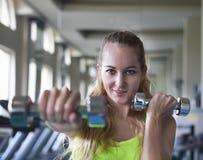Νέα γυναίκα με τα barbells στο υπόβαθρο γυμναστικής Στοκ εικόνα με δικαίωμα ελεύθερης χρήσης