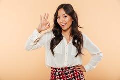 Νέα γυναίκα με την ασιατική εμφάνιση που παρουσιάζει εντάξει χειρονομία που είναι Στοκ Φωτογραφίες