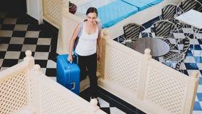 Νέα γυναίκα με την είσοδο βαλιτσών στο ξενοδοχείο στοκ φωτογραφία με δικαίωμα ελεύθερης χρήσης