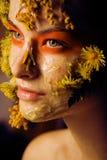 Νέα γυναίκα με την κίτρινη floral μάσκα σε την στενός επάνω προσώπου, έννοια μόδας makeup Στοκ Φωτογραφίες