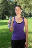Νέα γυναίκα με την κατανάλωση του μπουκαλιού κατά τη διάρκεια του αθλητισμού ή Στοκ φωτογραφία με δικαίωμα ελεύθερης χρήσης