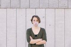 Νέα γυναίκα με την κοντή τρίχα που φυσά μια ρόδινη γόμμα φυσαλίδων Στοκ Εικόνα