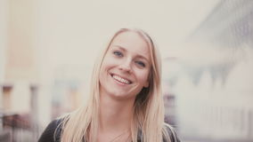 Νέα γυναίκα με την ξανθή μακρυμάλλη εξέταση τη κάμερα και το χαμόγελο Πορτρέτο του ελκυστικού κοριτσιού στο υπόβαθρο θαμπάδων πόλ απόθεμα βίντεο