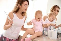 Νέα γυναίκα με την οδοντόβουρτσα και κόρη κοντά στον καθρέφτη στοκ φωτογραφίες