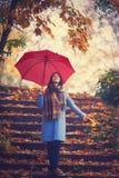 Νέα γυναίκα με την ομπρέλα και τα φύλλα Στοκ Εικόνα