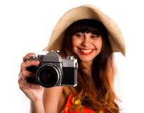 Νέα γυναίκα με την παλαιά φωτογραφική μηχανή, που χαμογελά παίρνοντας τις φωτογραφίες Στοκ Εικόνα