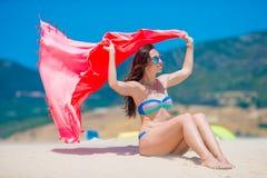 Νέα γυναίκα με την πετσέτα παραλιών κατά τη διάρκεια των τροπικών διακοπών Το όμορφο κορίτσι απολαμβάνει τις καλοκαιρινές διακοπέ Στοκ Φωτογραφίες