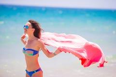 Νέα γυναίκα με την πετσέτα παραλιών κατά τη διάρκεια των τροπικών διακοπών Το όμορφο κορίτσι απολαμβάνει τις καλοκαιρινές διακοπέ Στοκ Εικόνα