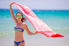 Νέα γυναίκα με την πετσέτα παραλιών κατά τη διάρκεια των τροπικών διακοπών Το όμορφο κορίτσι απολαμβάνει τις καλοκαιρινές διακοπέ Στοκ Φωτογραφία