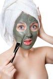 Νέα γυναίκα με την του προσώπου μάσκα στη SPA ομορφιάς. Στοκ Φωτογραφίες
